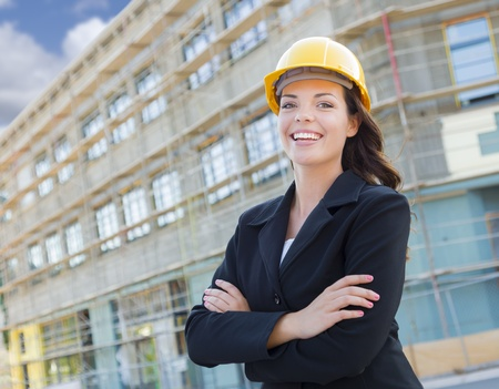 building contractor: Portrait of Young Attractive Professional Female Contractor Wearing Hard Hat at Construction Site.