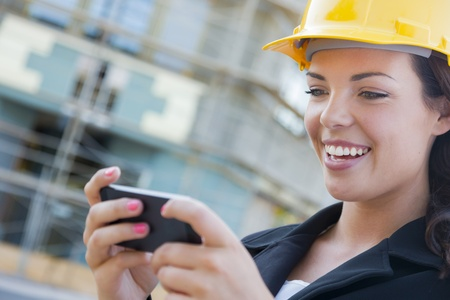 hard: Young Professional Female Contractor Wearing Hard Hat at Contruction Site Texting with Cell Phone.