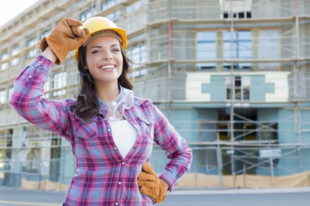 woman hard working: Portrait of Young Attractive Female Construction Worker Wearing Gloves, Hard Hat and Protective Goggles at Construction Site.