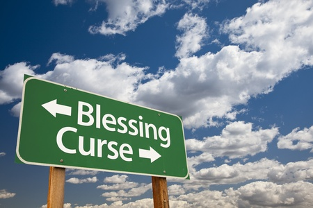 curse: Blessing, Curse Green Road Sign Over Dramatic Blue Sky and Clouds.
