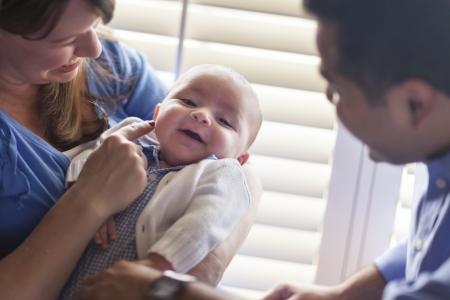 mixed race couple: Feliz pareja de raza mixta disfruta de su hijo reci�n nacido a la luz de la ventana. Foto de archivo