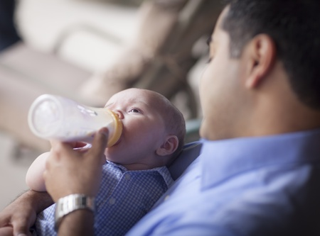 mixed race baby: Happy Hispanic Father Bottle Feeding His Very Content Mixed Race Son.
