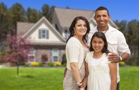 front of the house: Happy Hispanic Mother, Father and Daughter in Front of Their Home.