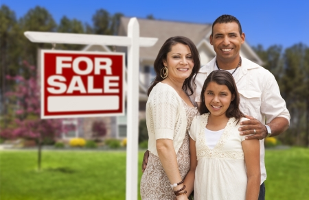 sales lady: Hispanic Mother, Father and Daughter in Front of Their New Home with Sold Home For Sale Real Estate Sign.