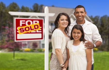 Hispanic Mother, Father and Daughter in Front of Their New Home with Sold Home For Sale Real Estate Sign. Stock Photo - 20998981