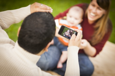 Happy Mixed Race Parents and Baby Boy Taking Self Portraits Outside at the Park. photo