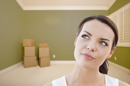 Attractive Daydreaming Young Woman in Empty Green Room with Boxes. photo