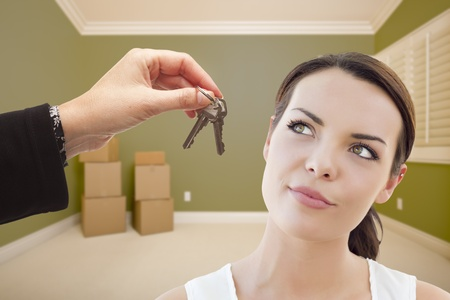 selling house: Attractive Young Woman Being Handed The Keys in Empty Green Room with Boxes. Stock Photo