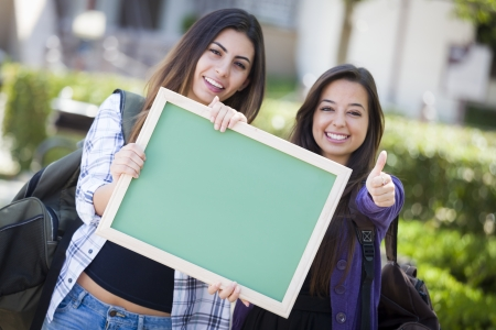 18's: Portrait of Two Attractive Mixed Race Female Students Holding Blank Chalkboard with Thumbs Up and Carrying Backpacks on School Campus. Stock Photo