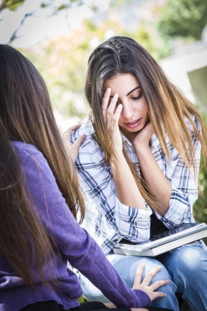Sad or Stressed Young Mixed Race Girl Being Comforted By Her Friend Outside on Bench. photo