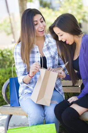 palestinian: Two Young Adult Mixed Race Women Looking Into Their Shopping Bags Outside on Bench. Stock Photo