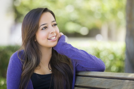 school campus: Happy Mixed Race Female Student Portrait on School Campus Bench. Stock Photo
