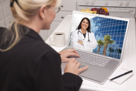 Over Shoulder of Woman In Kitchen Using Laptop - Online Chat with Nurse or Doctor on Screen. photo