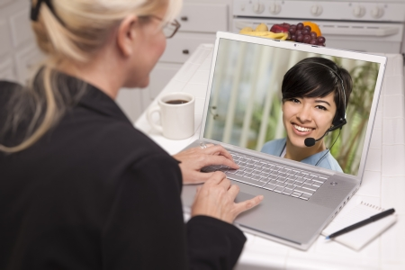 video conference: Over Shoulder of Woman In Kitchen Using Laptop - Online Chat with Nurse or Doctor on Screen. Stock Photo