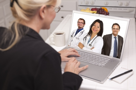 wide screen: Over Shoulder of Woman In Kitchen Using Laptop Online Chat with Nurses or Doctors on Screen.
