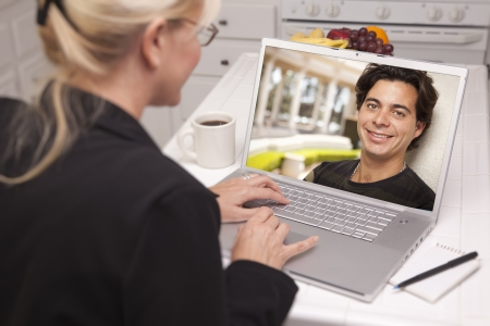 Happy Young Woman In Kitchen Using Laptop Online Dating Search with Portrait of Man On Screen. photo