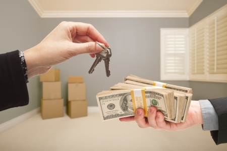 short sale: Man and Woman Handing Over Cash For House Keys Inside Empty Gray Room with Boxes.