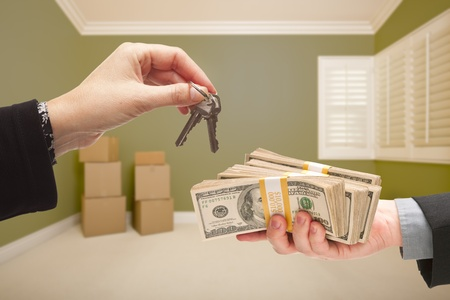 short sale: Man and Woman Handing Over Cash For House Keys Inside Empty Green Room with Boxes. Stock Photo