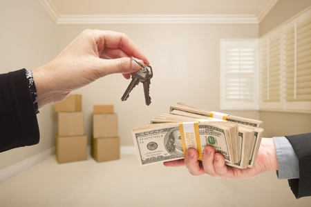 cash box: Man and Woman Handing Over Cash For House Keys Inside Empty Tan Room with Boxes. Stock Photo