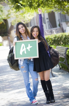 palestinian: Excited Mixed Race Female Students Holding Chalkboard With A+ Written on it.