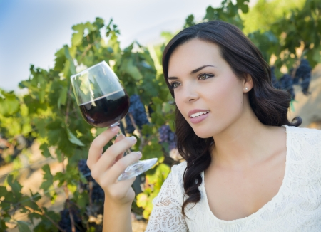wine country: Pretty Mixed Race Young Adult Woman Enjoying A Glass of Wine in the Vineyard.