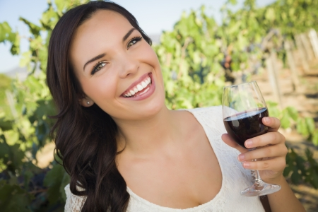 Pretty Mixed Race Young Adult Woman Enjoying A Glass of Wine in the Vineyard. photo