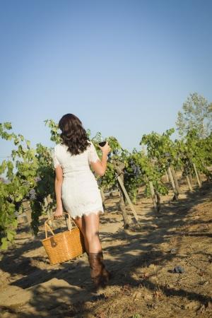 Jong gemengd ras vrouw genieten van een wandeling en een glas wijn in de wijngaard.