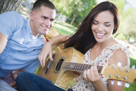 girl playing guitar: Happy Mixed Race Couple at the Park Playing Guitar and Singing Songs.