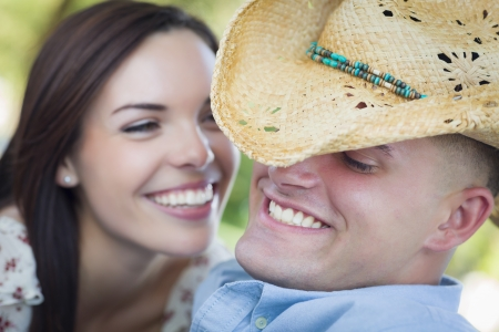 mixed race couple: Happy Mixed Race Romantic Couple with Cowboy Hat Flirting in the Park.