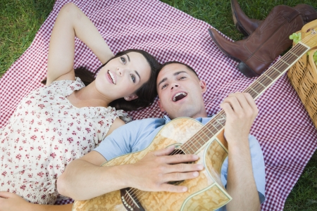 picnic blanket: Happy Mixed Race Couple On Picnic Blanket at the Park Playing Guitar and Singing Songs.