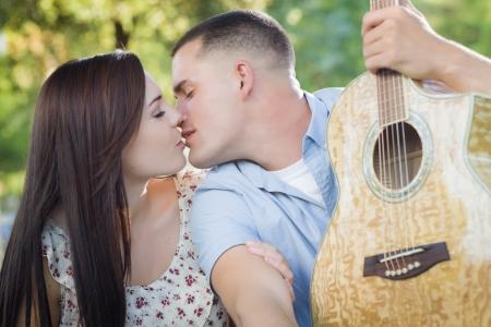 mixed race couple: Cari�osa pareja raza mixta retrato con la guitarra en el parque.