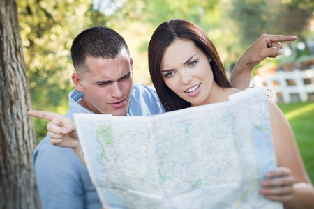 Lost and Confused Mixed Race Couple Looking Over A Map Outside Together. photo