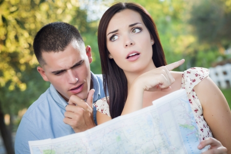 confused person: Lost and Confused Mixed Race Couple Looking Over A Map Outside Together.