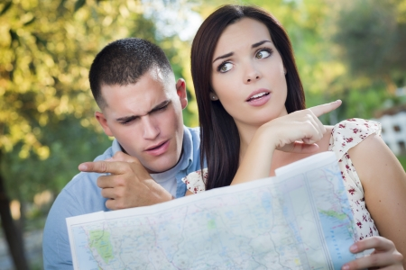 error: Lost and Confused Mixed Race Couple Looking Over A Map Outside Together.