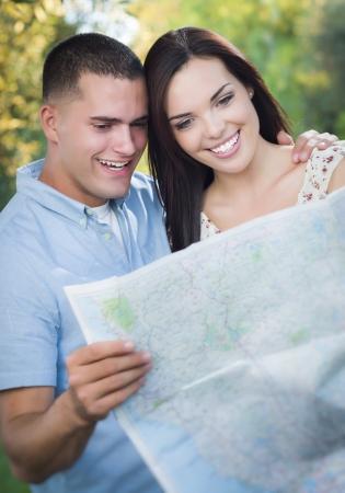 mixed race couple: Feliz pareja de raza mixta mirando en un mapa fuera Together.