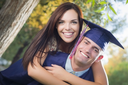 Happy Male Graduate in Cap and Gown and Pretty Girl Celebrate Outside. photo