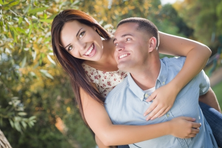 adult dating: Happy Mixed Race Romantic Couple Piggyback Portrait in the Park.