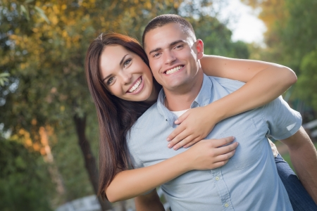 Happy Mixed Race Romantic Couple Piggyback Portrait in the Park. photo