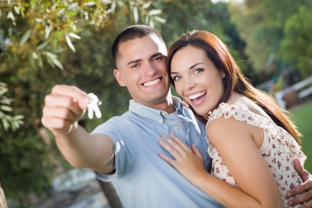 Happy Excited Mixed Race Couple with New House Keys Outside. photo