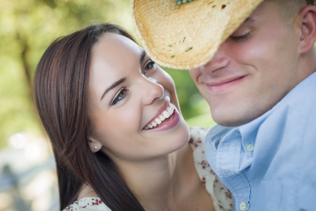Happy Mixed Race Romantic Couple with Cowboy Hat Flirting in the Park. photo