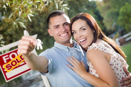 Mixed Race Excited Military Couple with New House Keys and Sold Real Estate Sign Outside. photo