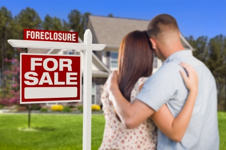 Military Couple in Front of House and Foreclosure For Sale Real Estate Sign. photo