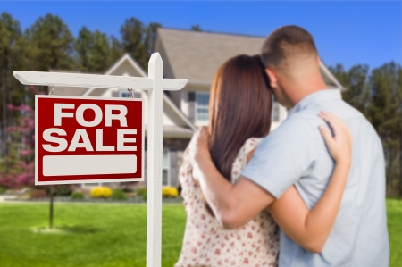 outside of house: For Sale Real Estate Sign and Affectionate Military Couple Looking at Nice New House.