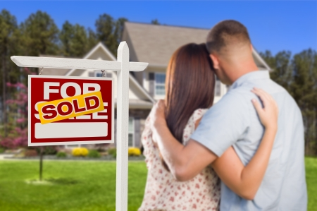 for sale sign: Sold For Sale Real Estate Sign and Affectionate Military Couple Looking at Nice New House. Stock Photo