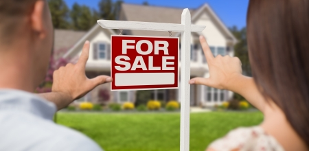 For Sale Real Estate Sign, House and Military Couple Framing Hands in Front. photo