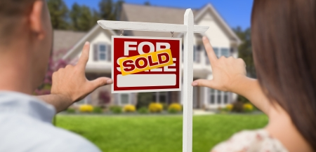 Sold For Sale Real Estate Sign, House and Military Couple Framing Hands in Front. photo