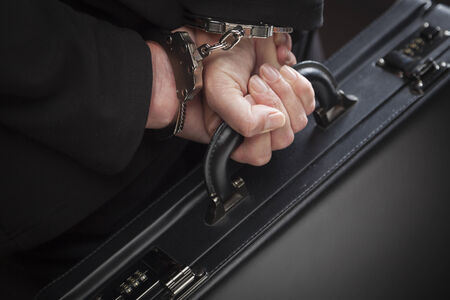 cuffed: Woman Wearing Handcuffs Carrying Briefcase In Dramatic Lighting. Stock Photo