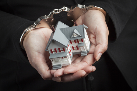 cuffed: Woman In Handcuffs Holding Small House Against Black. Stock Photo