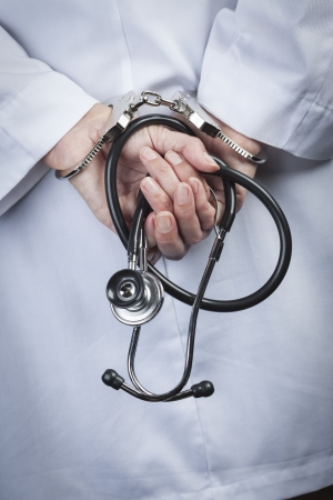 con man: Female Doctor or Nurse In Handcuffs and Lab Coat Holding Stethoscope.