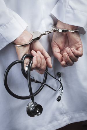 Female Doctor or Nurse In Handcuffs and Lab Coat Holding Stethoscope. photo